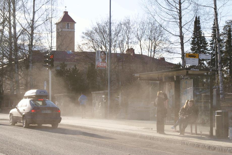 Auto nostaa ilmaan katupölyä bussipysäkillä.